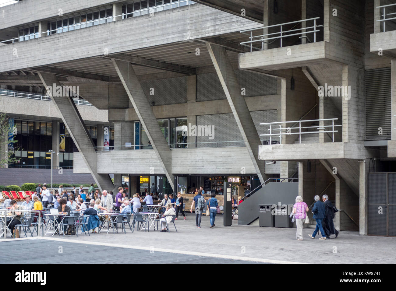 People sat outside the brutalist architecture of the National Theatre on London's South Bank, London, UK - Stock Image