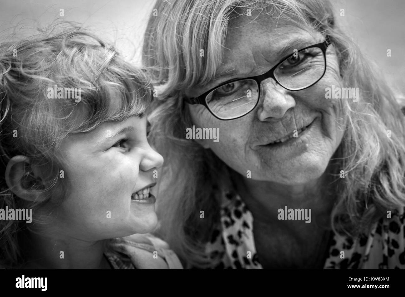 Young girl looks to her grandmother with pure happiness in a black and white photograph. Often times we forget about - Stock Image