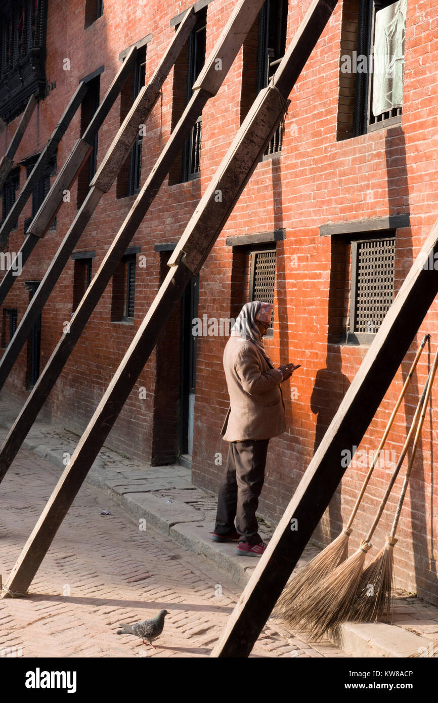 Man on cellphone stands next to earthquake damaged building propped up with wooden supports in Kathmandu, Nepal - Stock Image