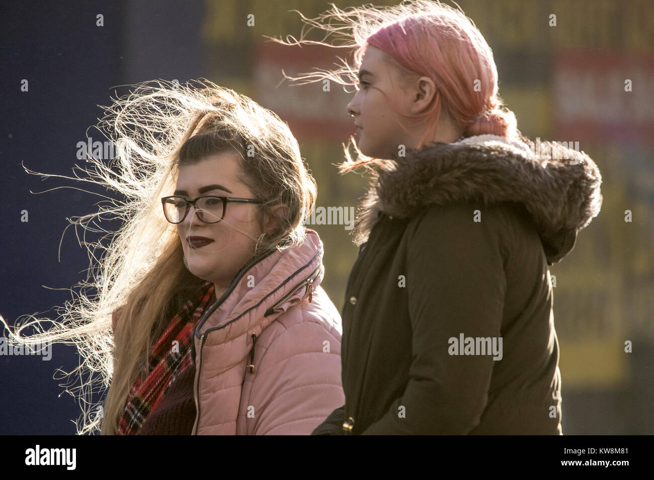 breezy outside wind blown hair windswept windy blowing mess messy weather season bad day winter wintry girls womens - Stock Image
