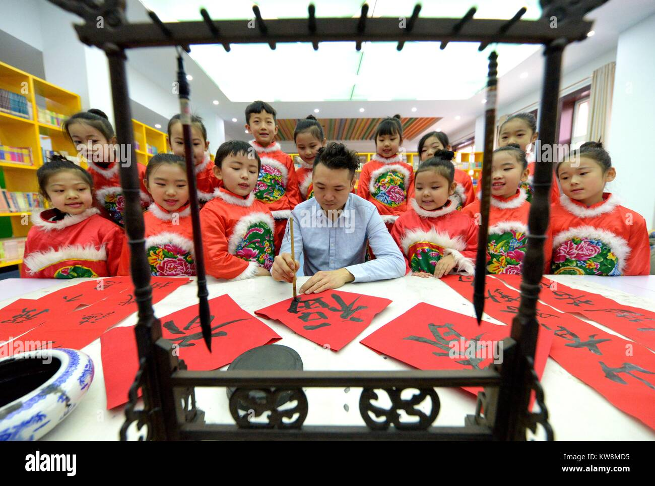 Shijiazhuang. 31st Dec, 2017. A teacher shows primary school students Chinese calligraphy during an extracurricular Stock Photo