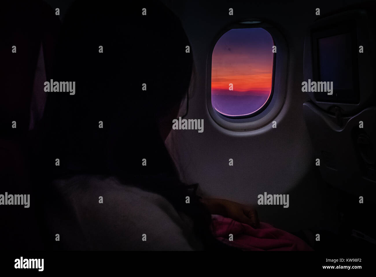 view from inside an airplane to sunset outside - Stock Image