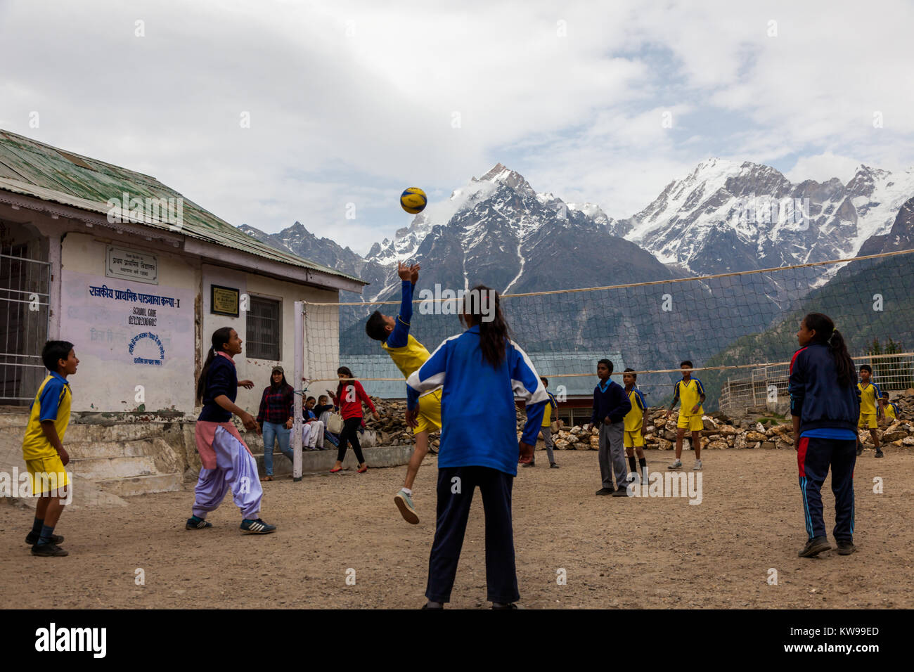 School children playing volleyball in school premise at Kalpa, Himachal Pradesh against the snow capped himalayan - Stock Image