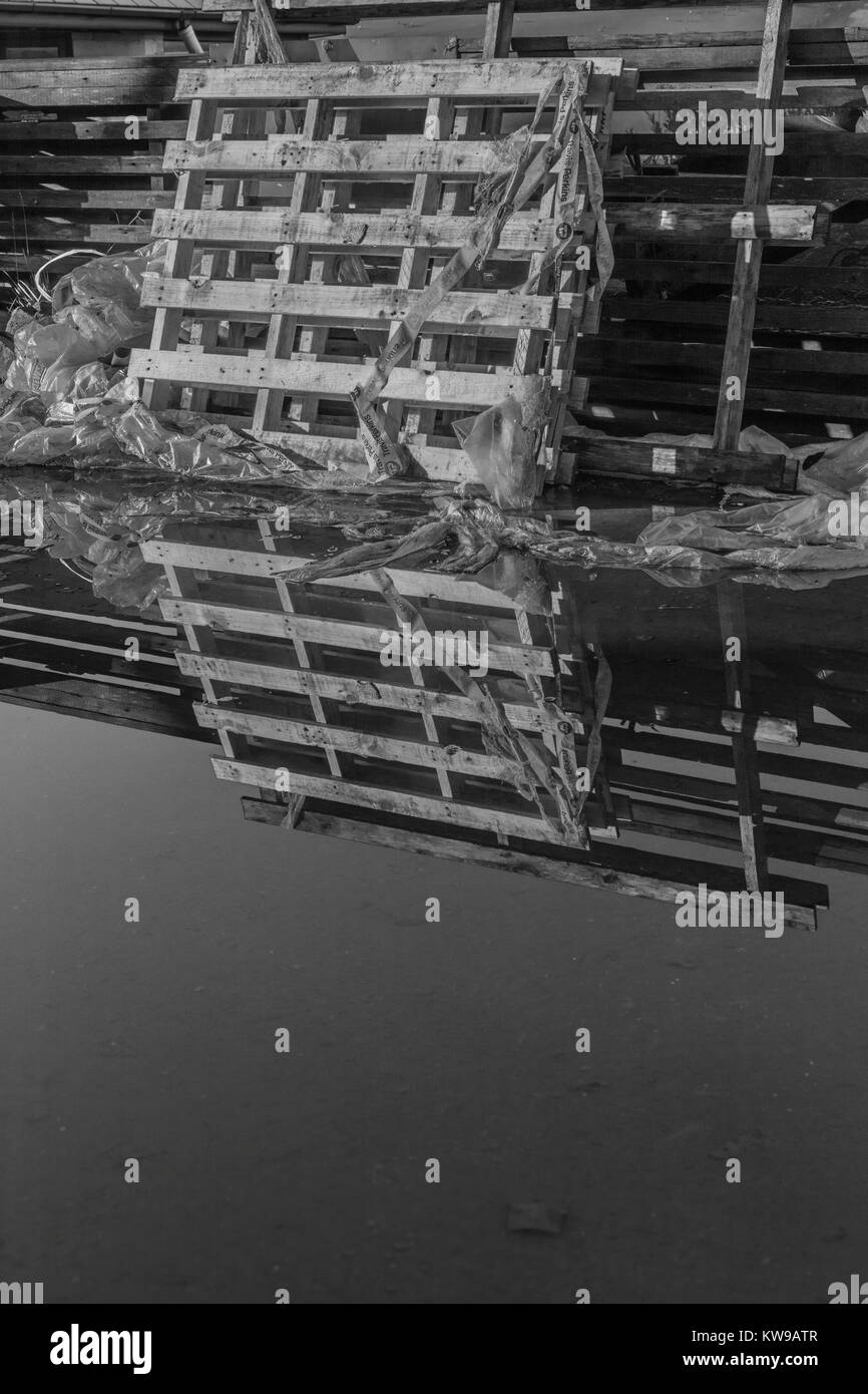 Black & white image of building supplies pallet reflected in water at a small construction site - metaphor for - Stock Image