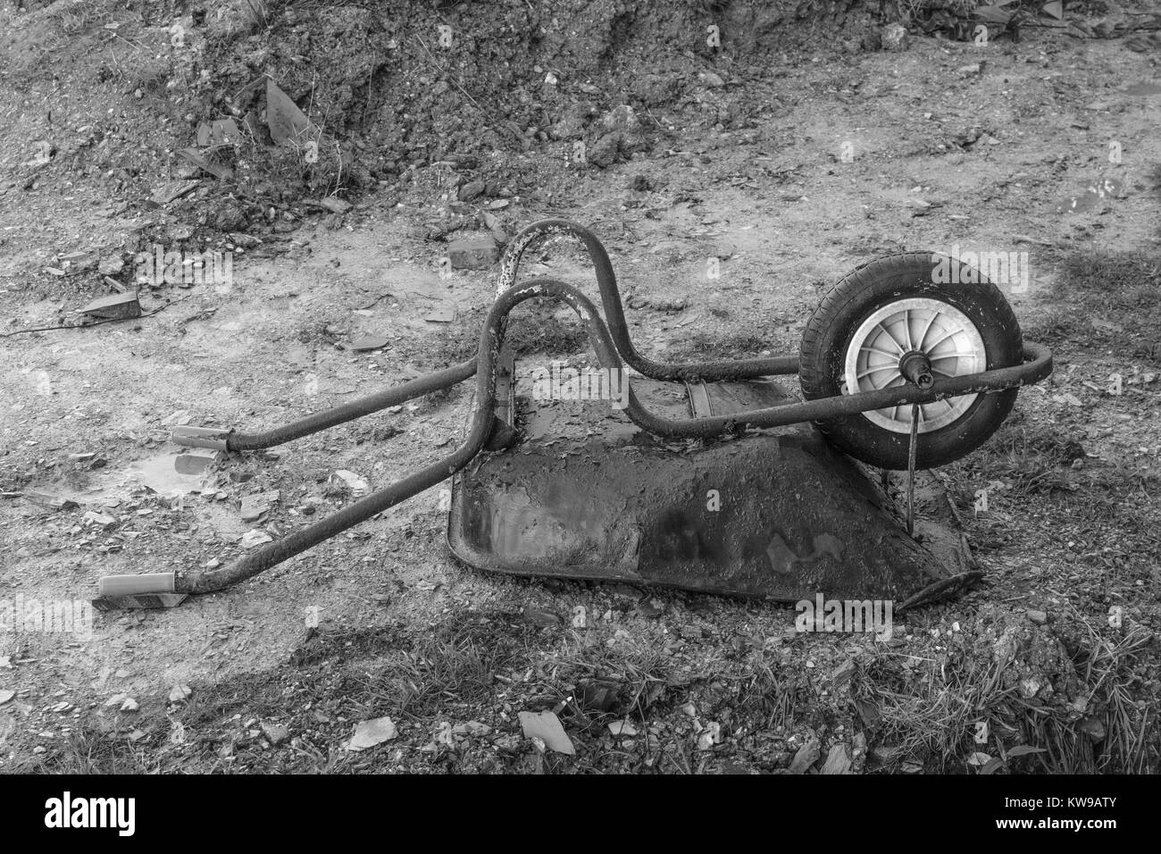 Black and white image (colour conversion) of turned wheelbarrow on small construction site - metaphor for downturn - Stock Image