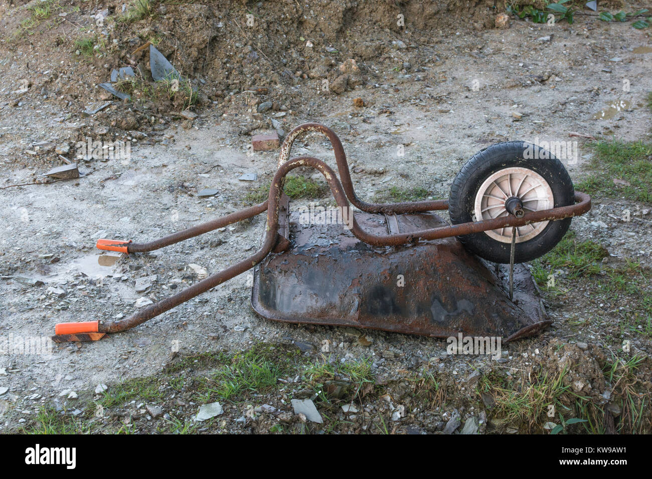 Upturned wheelbarrow on small construction site - metaphor for downturn in the construction industry. - Stock Image