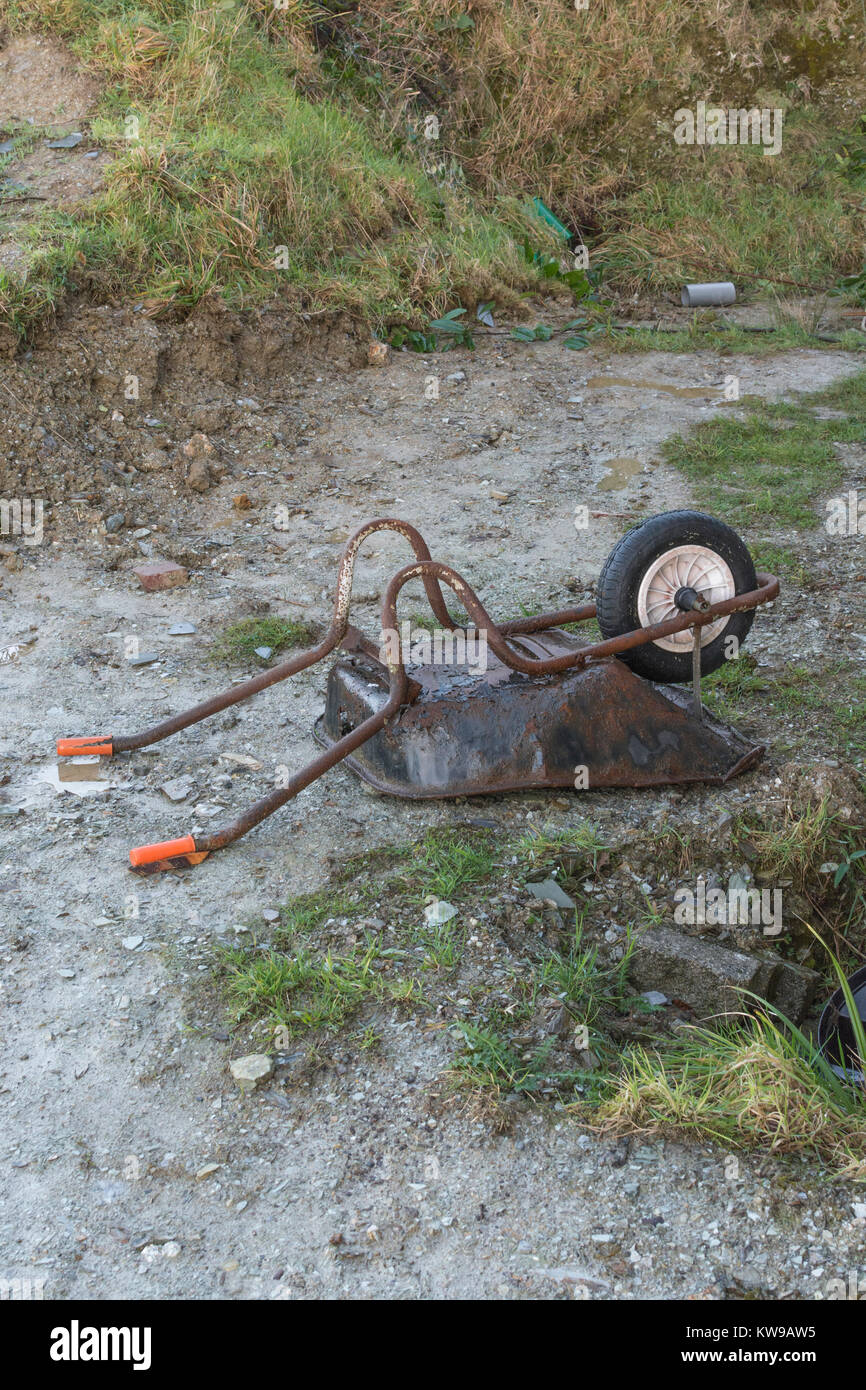 Upturned wheelbarrow on small construction site - metaphor for downturn in the construction industry - with copy - Stock Image