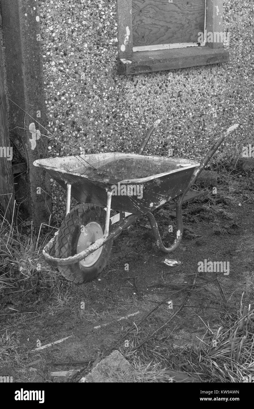 Black and white (colour conversion) image of a water-filled wheelbarrow at a small constructions site. - Stock Image