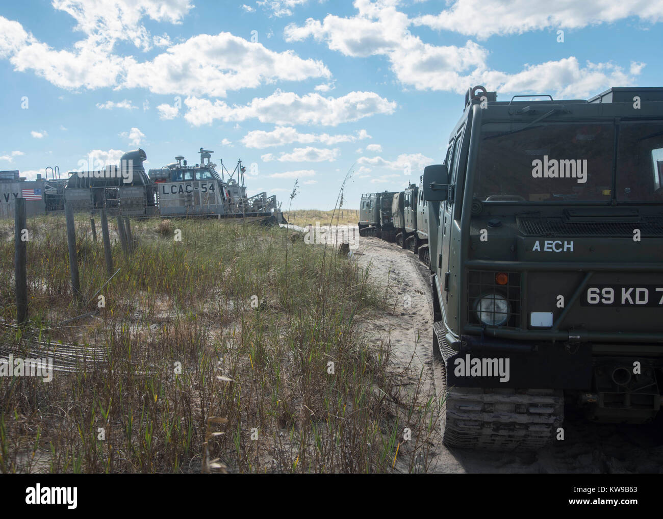 Armored vehicles idle on a beach after offloading from landing craft air cushion (LCAC) 54, attache - Stock Image