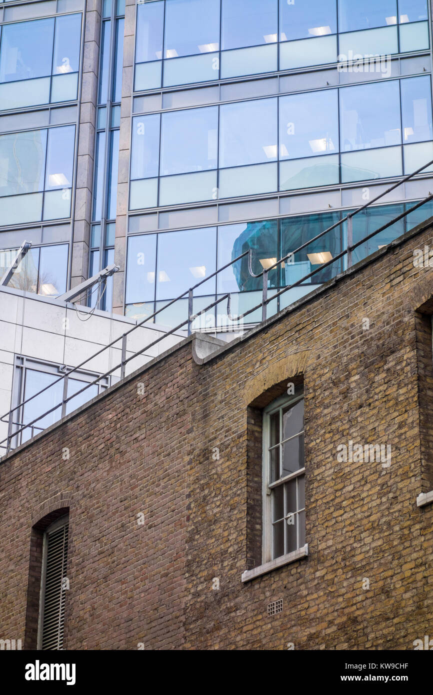 Old brick building and modern glazed building (One Silk Street) viewed from Milton Street, City of London, UK. Old - Stock Image