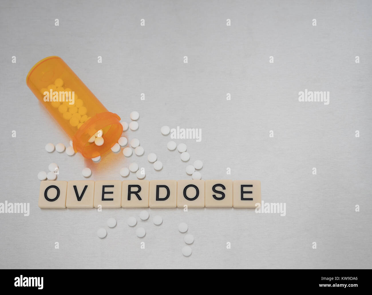 Overdose spelled with tile letters placed in a row with an open bottle of oxycodone tablets. Photographed from above - Stock Image