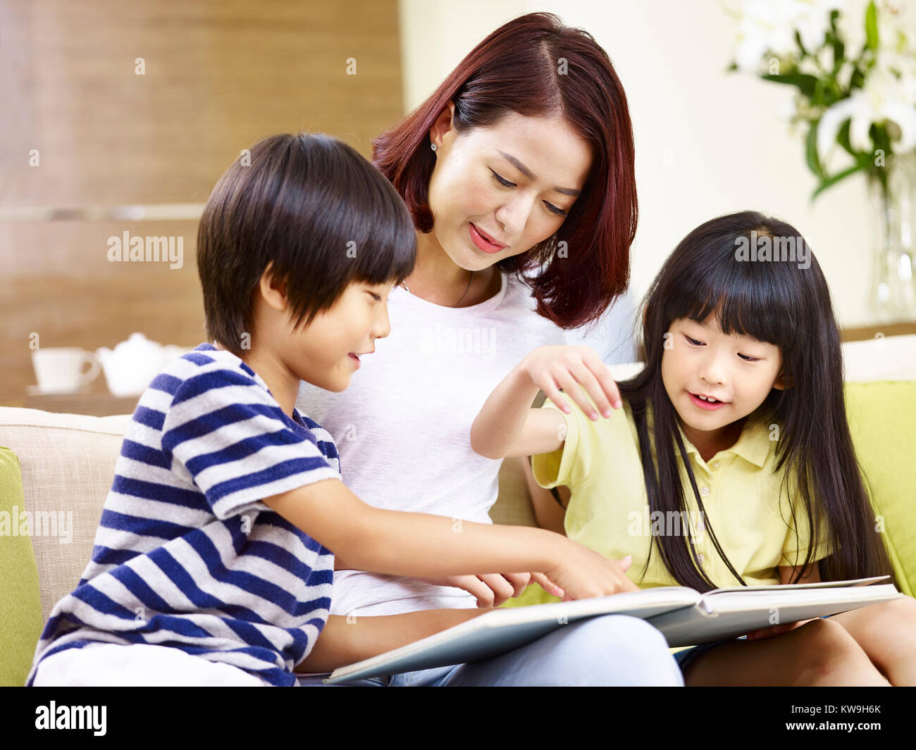 young asian mother and her son and daughter sitting on couch reading a book together. - Stock Image