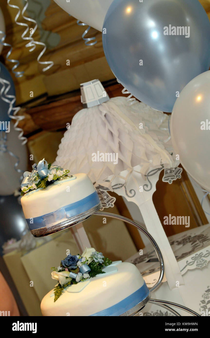 a wedding cake in three tiers on a table along with other table decorations for the big wedding day. Getting married - Stock Image
