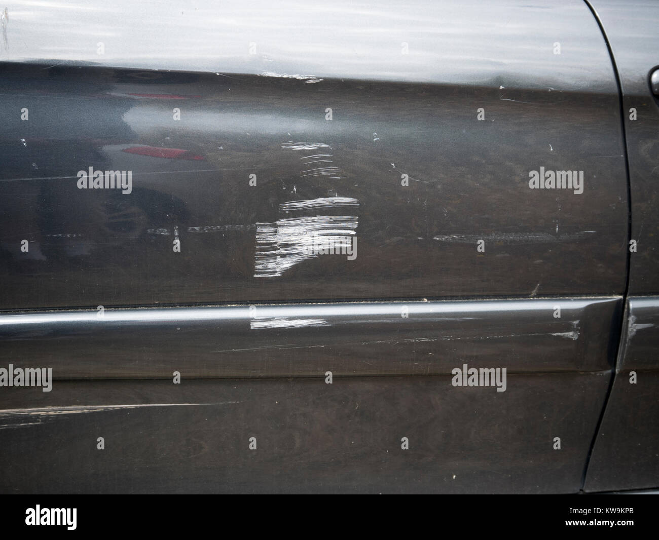 Scratches on the rear wing of a black car - Stock Image