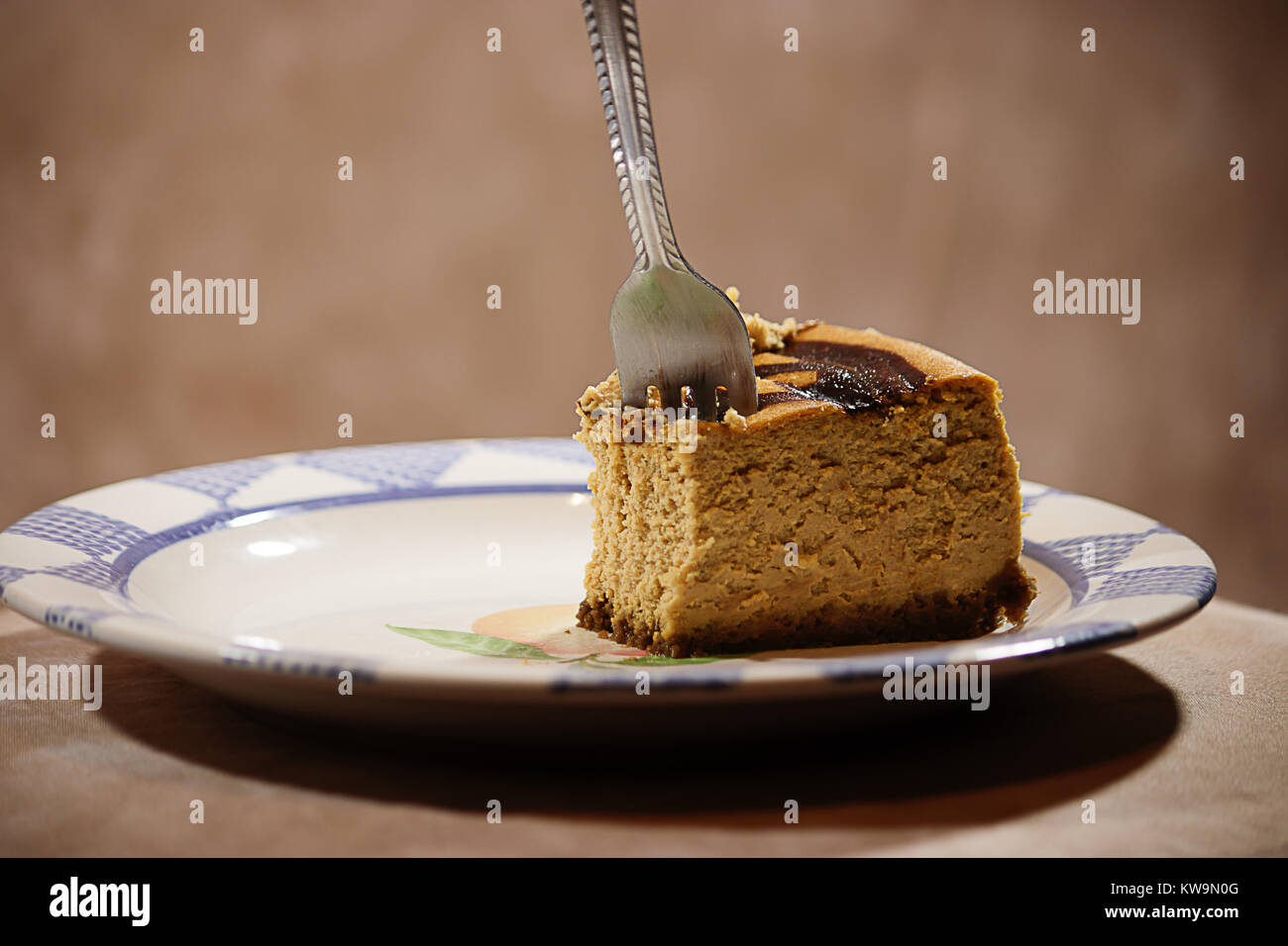 fork stuck in part of a pumpkin cheesecake against brown background - Stock Image