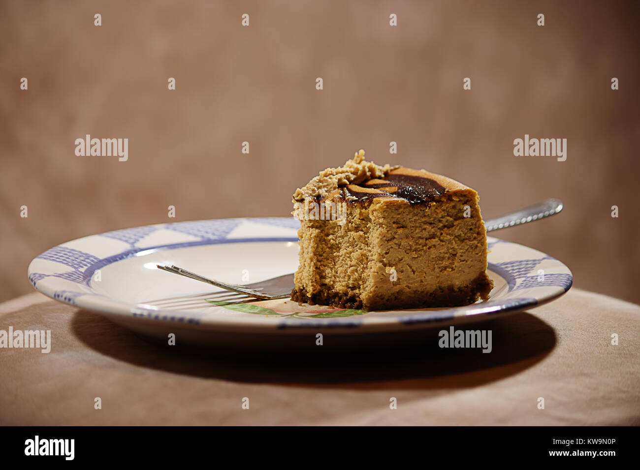 piece of pumpkin cheesecake against brown background - Stock Image