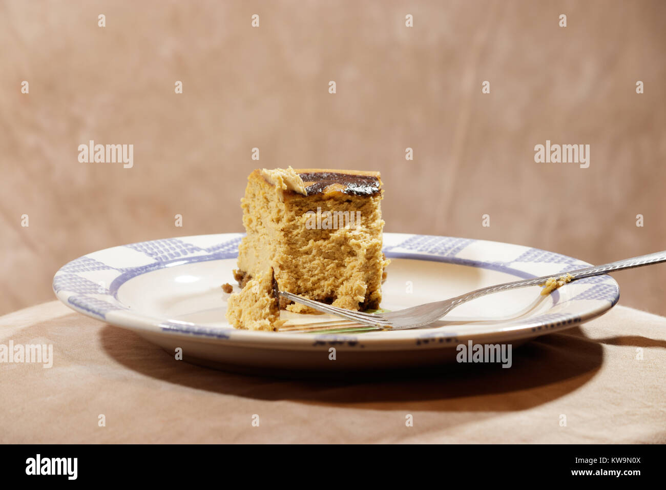 part of a pumpkin cheesecake with plate and fork - Stock Image