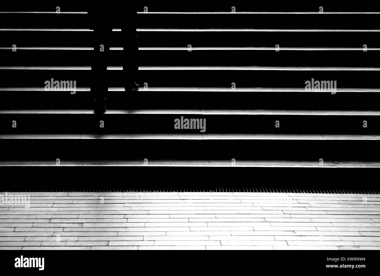 Silhouette shadow of person legs walking up the public stairs in subway passage on the night in black and white Stock Photo