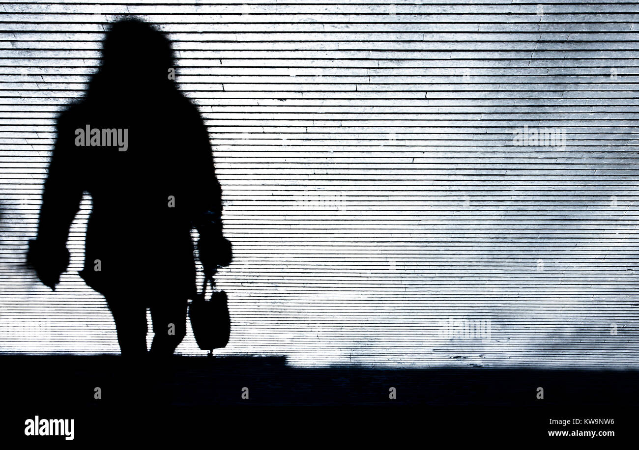 Blurry shadow silhouette of a woman walking the city street patterned sidewalk in the night in black and white - Stock Image
