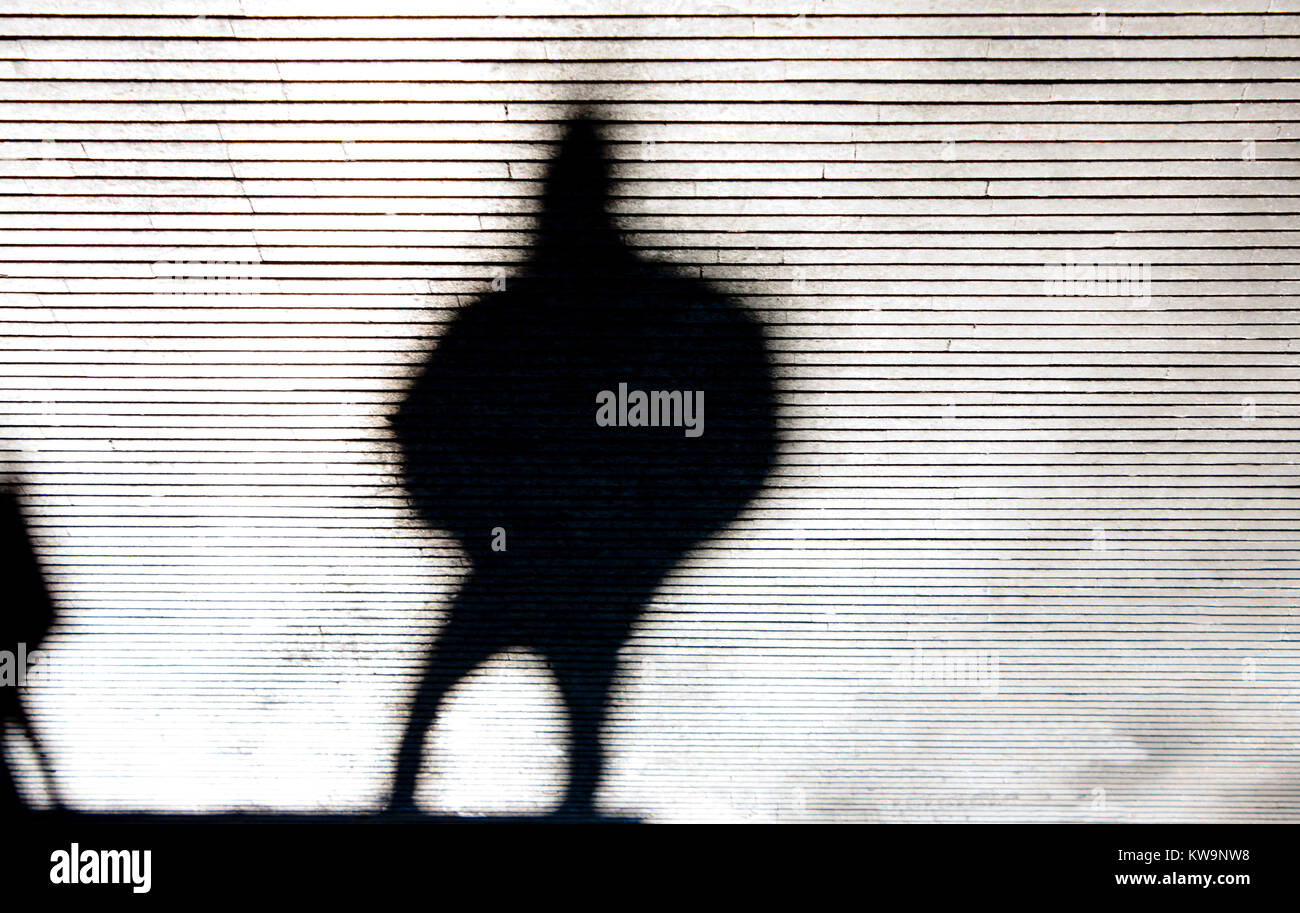 Blurry crooked shadow silhouette of a person walking city street patterned sidewalk in black and white - Stock Image