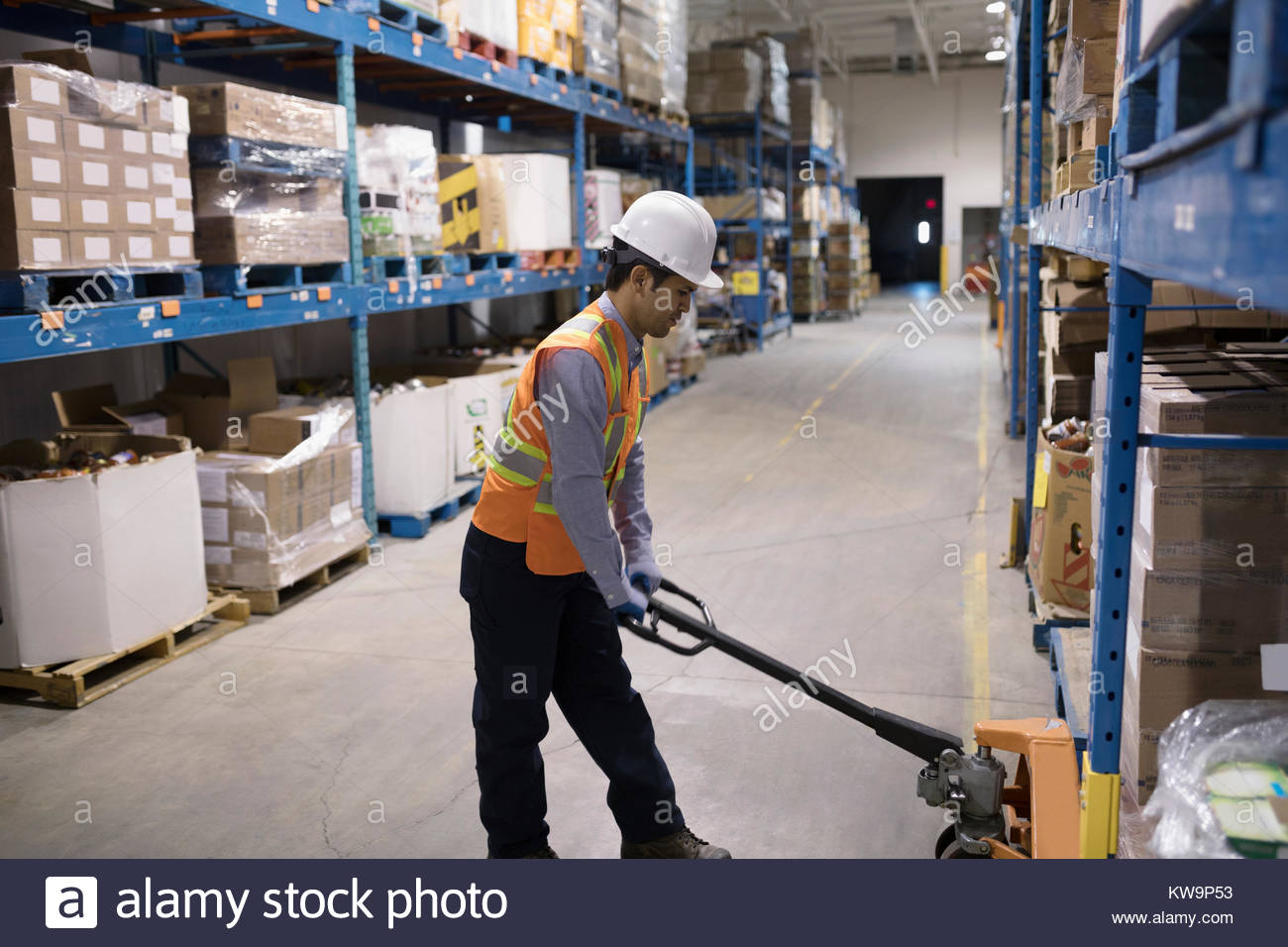 Worker using pallet jack in distribution warehouse - Stock Image