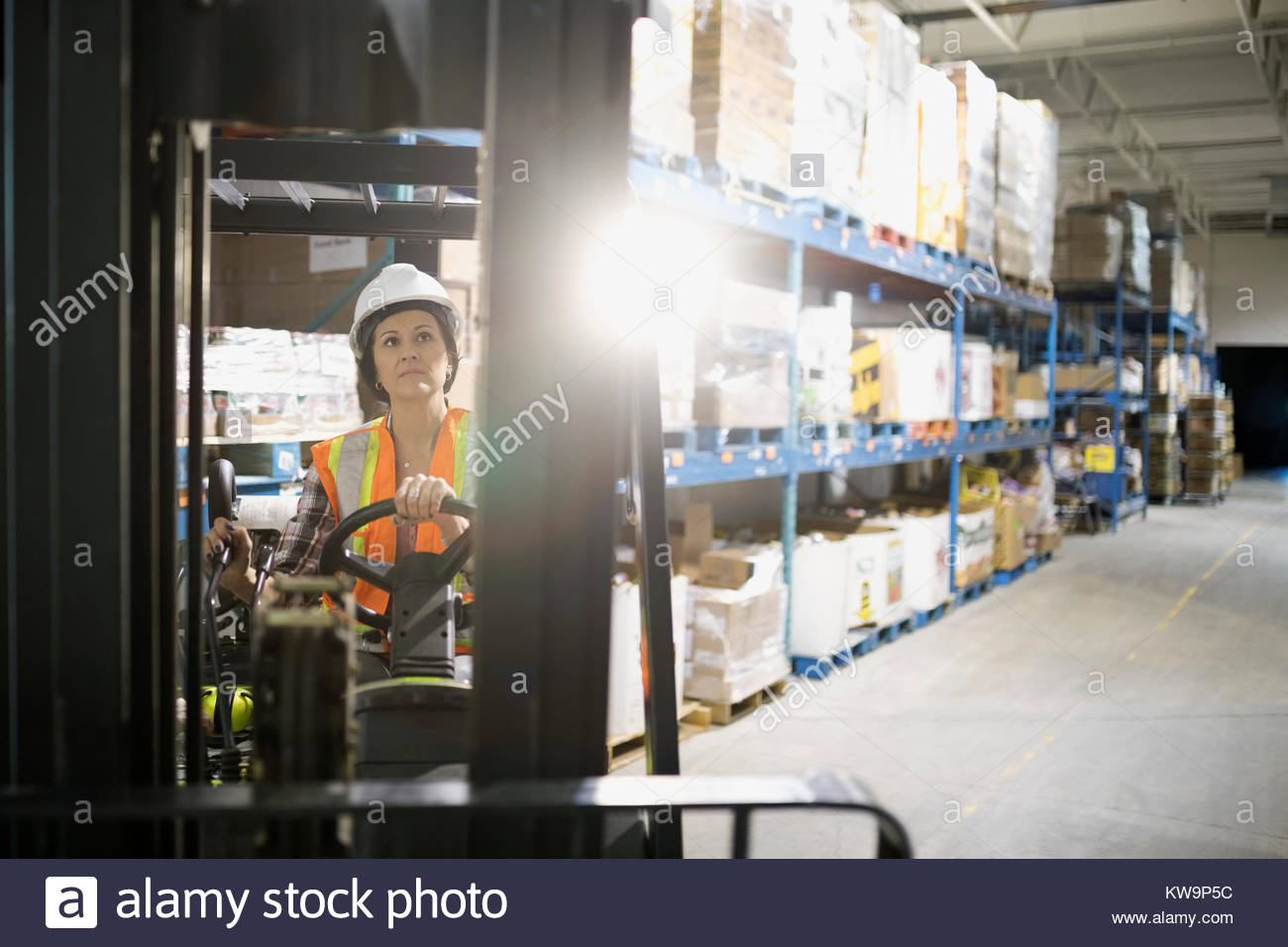 Female worker driving forklift in distribution warehouse - Stock Image