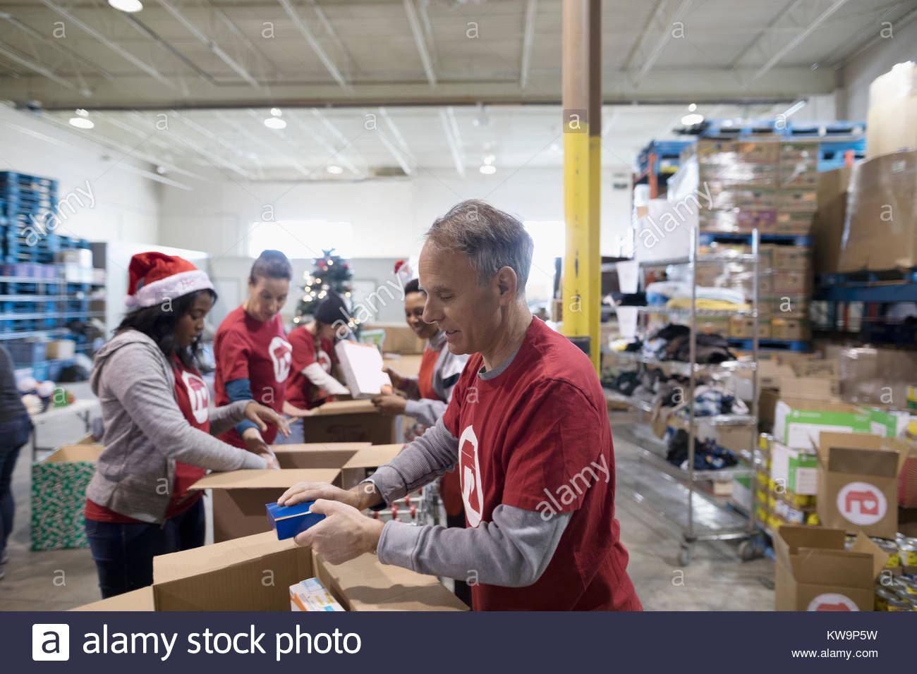 Male volunteer filling Christmas donation boxes in warehouse - Stock Image