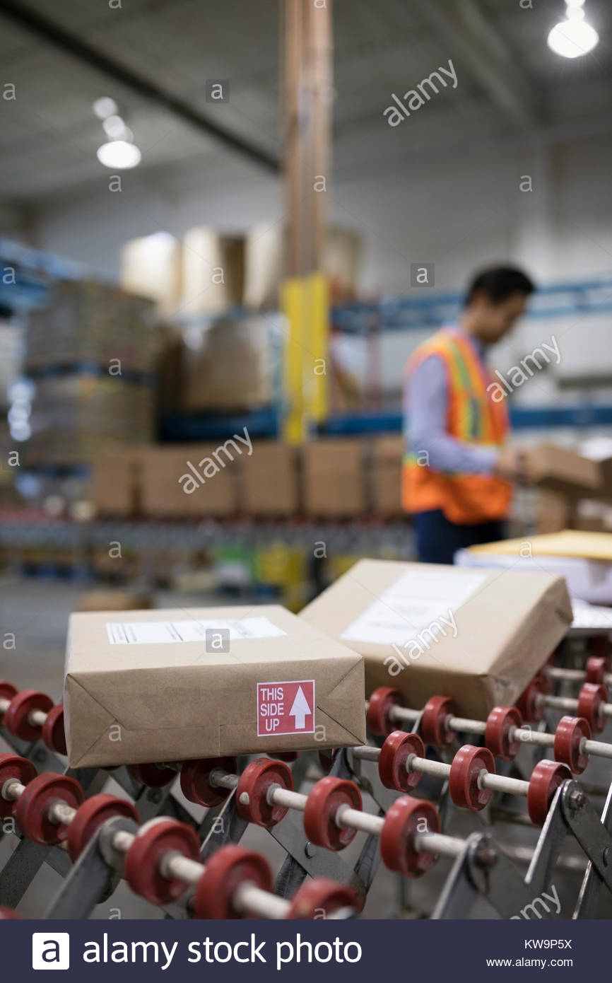 Packages on shipping warehouse production line conveyor belt - Stock Image