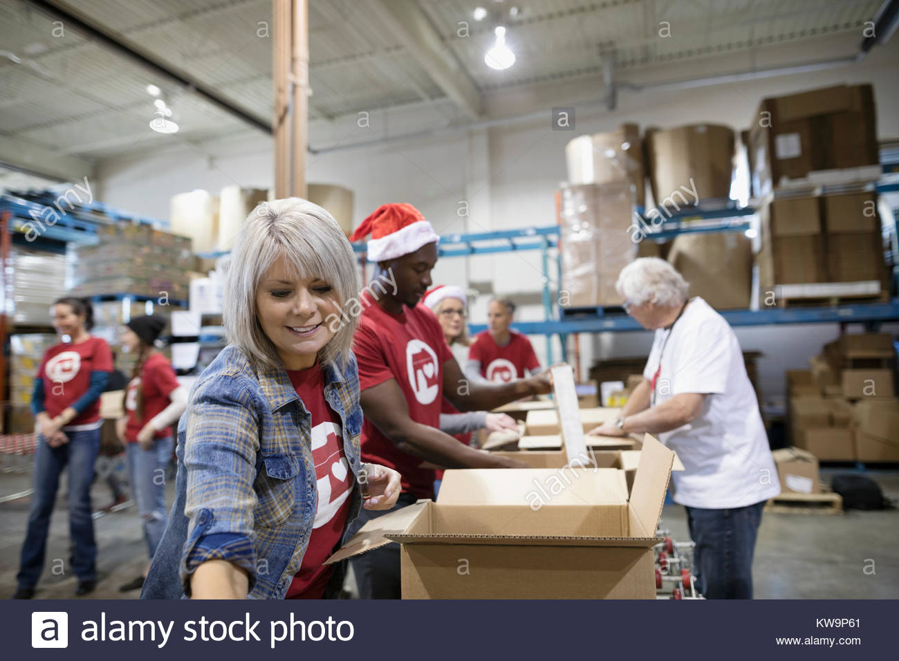 Female volunteer filling Christmas donation boxes in warehouse - Stock Image
