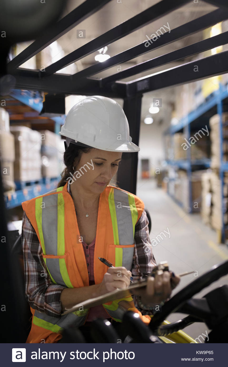 Female worker with clipboard driving forklift in distribution warehouse - Stock Image
