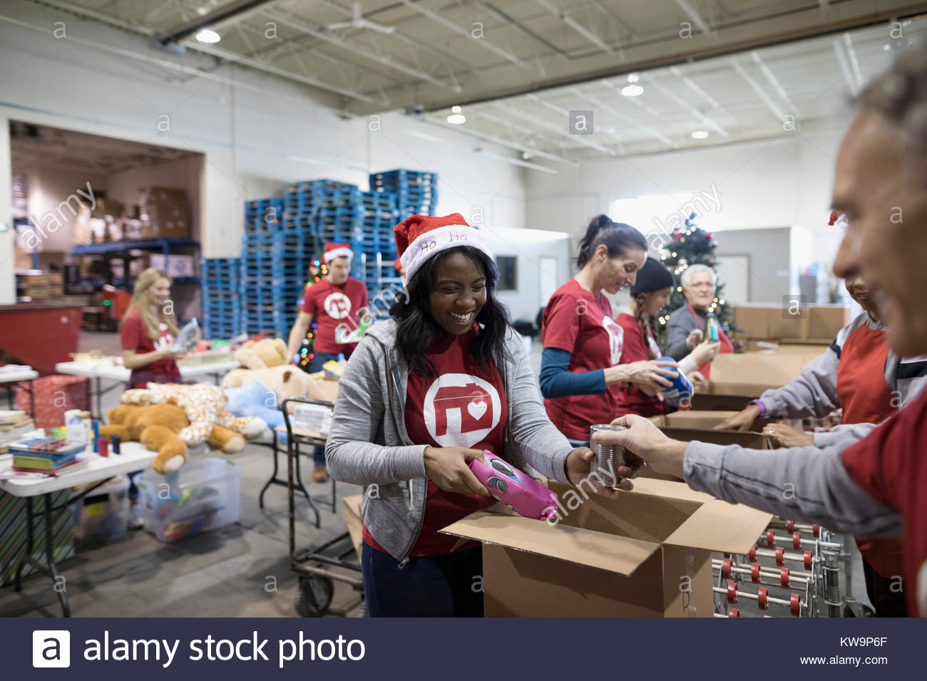 Female volunteer in Santa hat filling Christmas donation boxes in warehouse - Stock Image