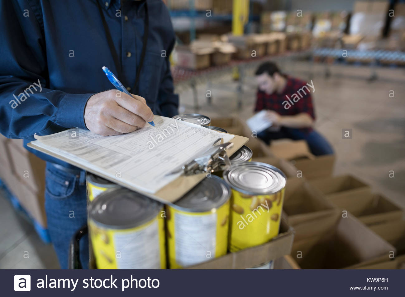Male volunteer with clipboard managing food drive in warehouse - Stock Image
