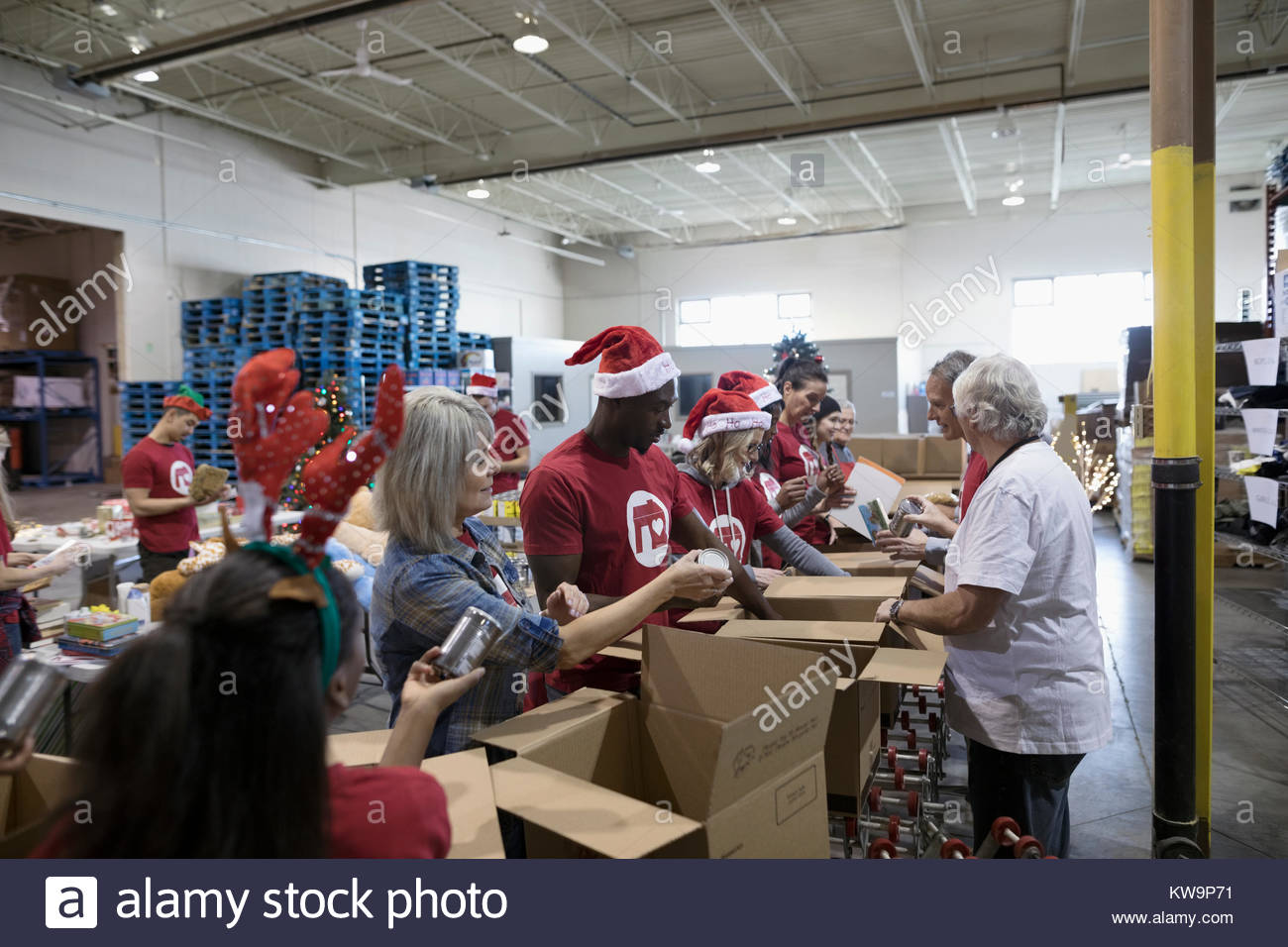 Volunteers in Santa hats filling Christmas donation boxes in warehouse - Stock Image