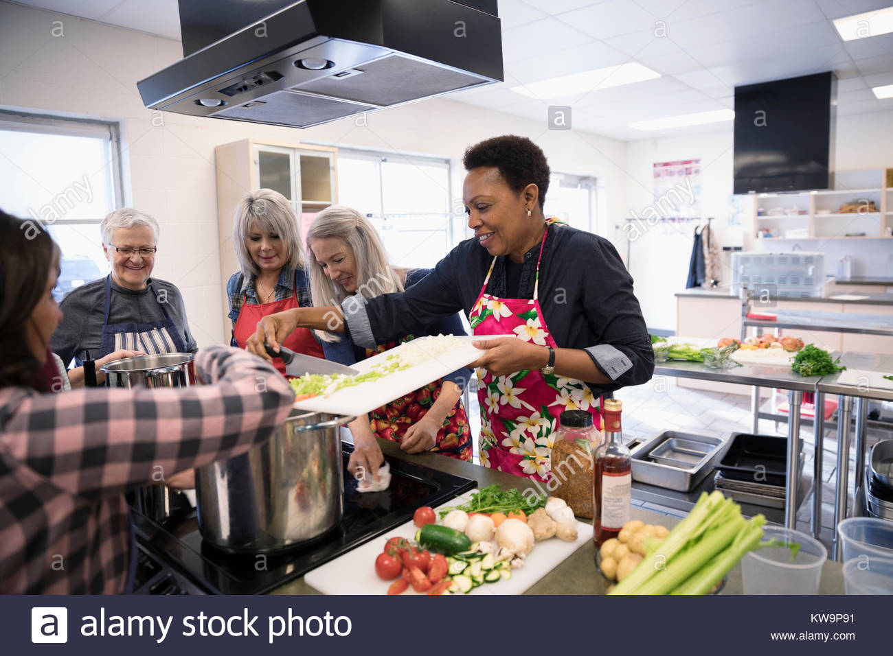 Female Volunteers Cooking In Soup Kitchen   Stock Image