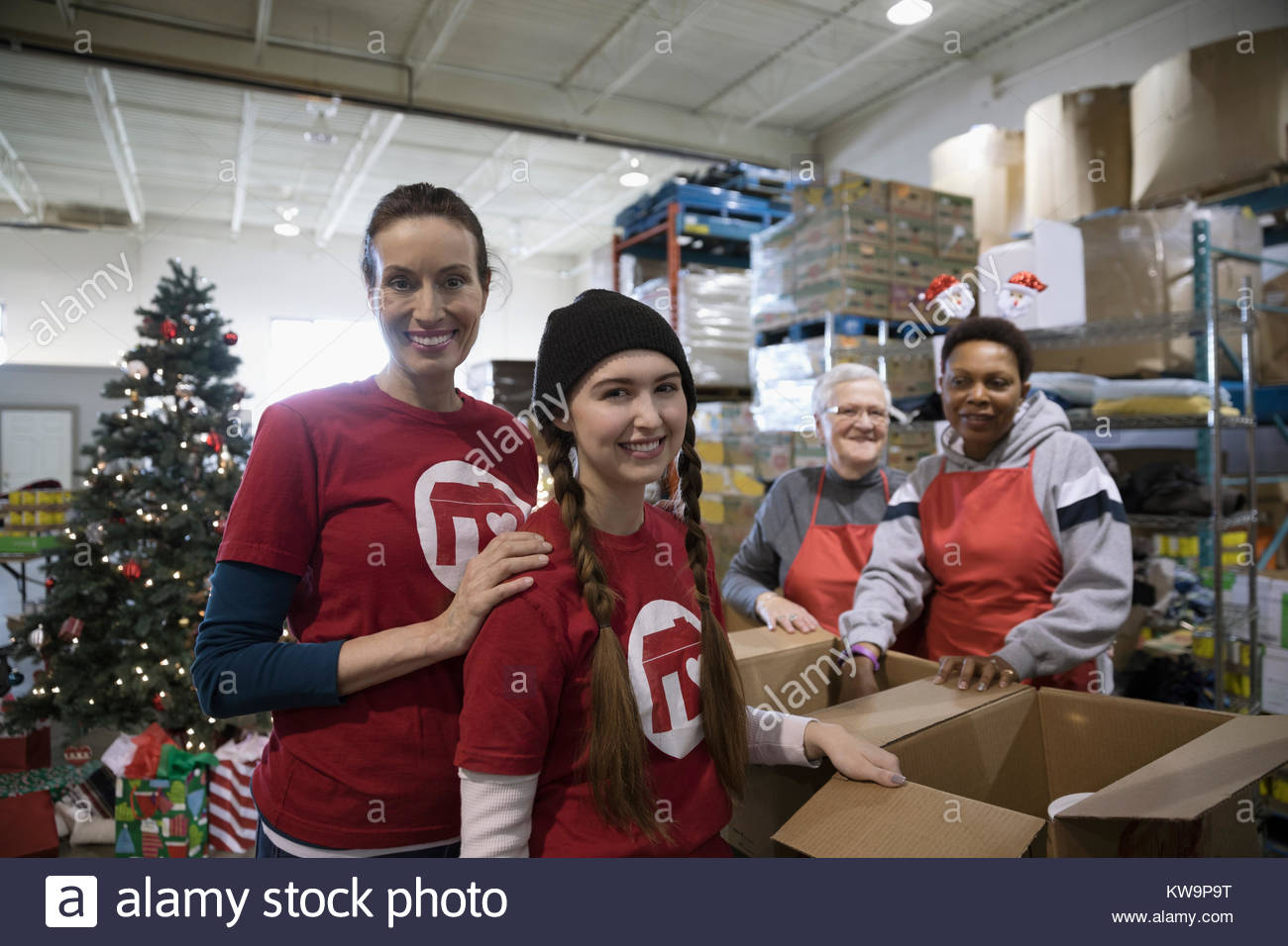 Portrait confident female volunteers filling Christmas donation boxes in warehouse - Stock Image