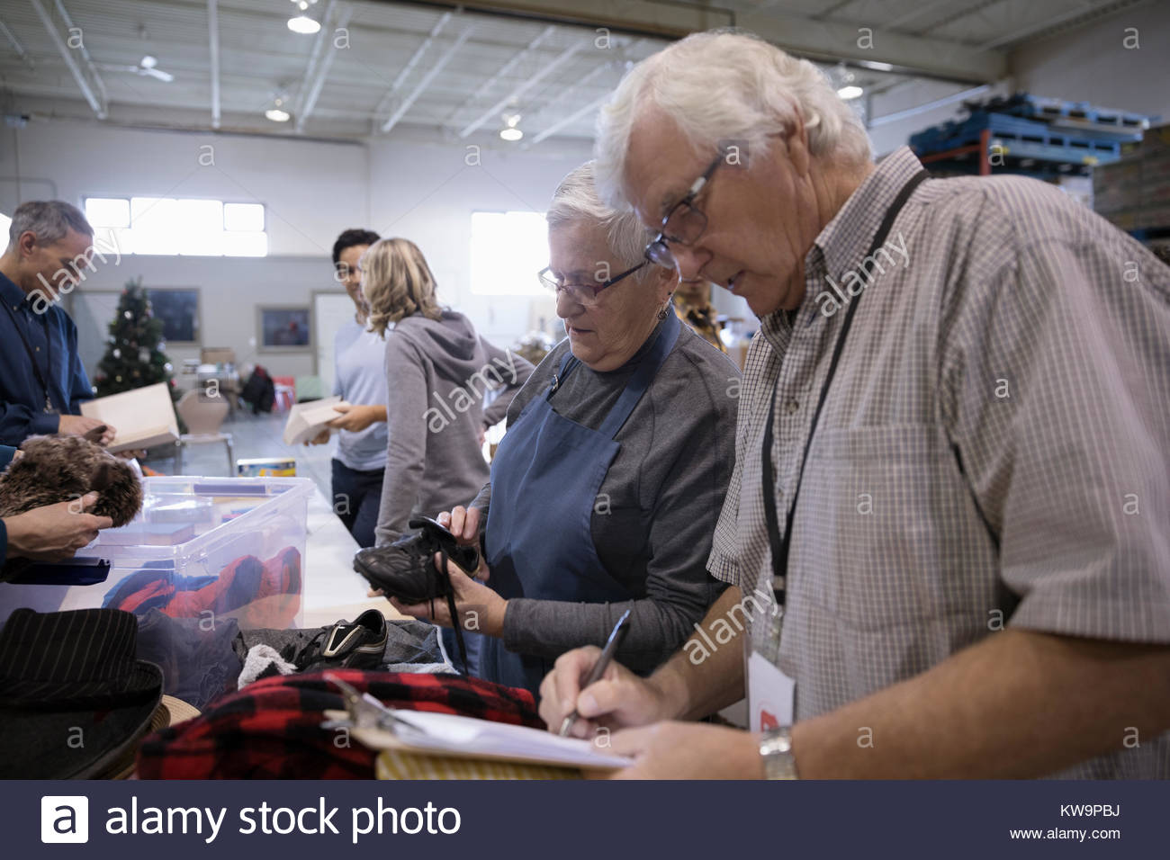 Senior couple with clipboard at clothing drive in warehouse - Stock Image