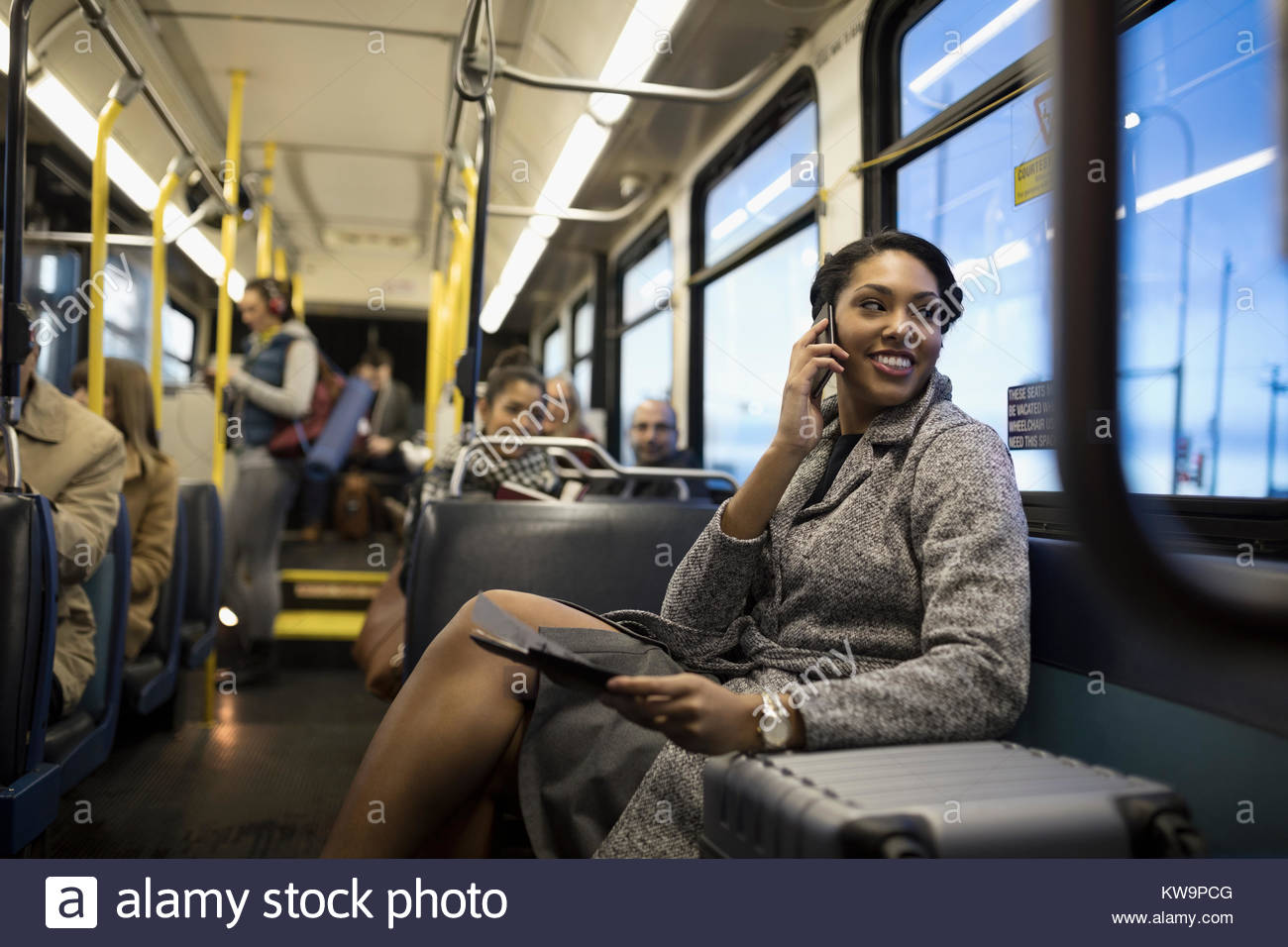 Smiling businesswoman commuter with suitcase talking on cell phone on bus - Stock Image