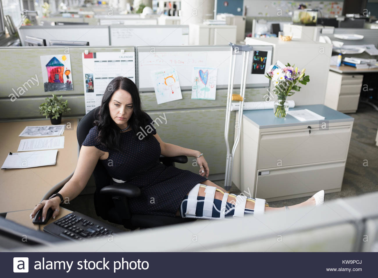 Businesswoman with broken leg in brace working at computer with feet up in office cubicle - Stock Image