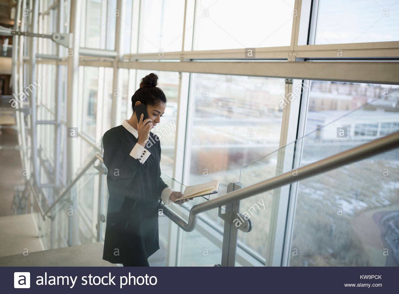 Businesswoman talking on cell phone and checking schedule on office stairs - Stock Image