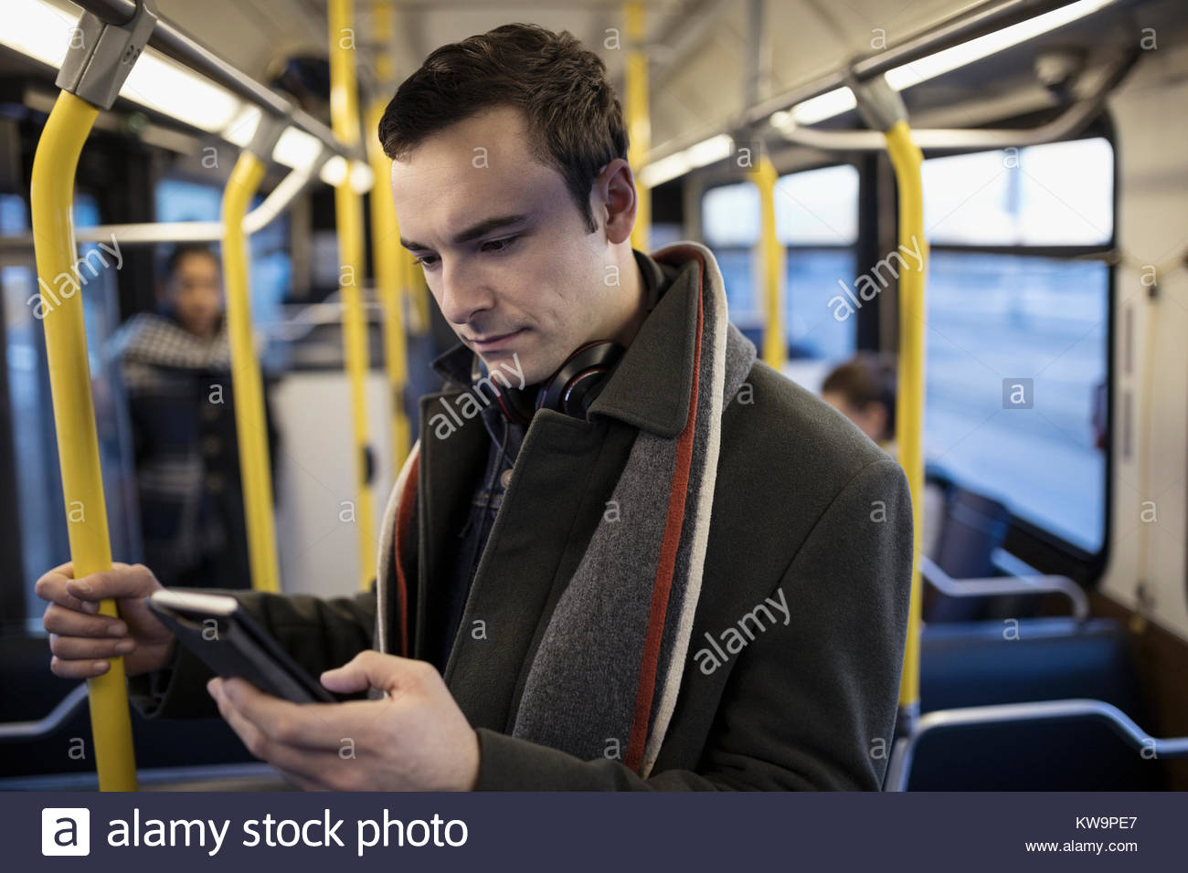 Businessman commuter texting with smart phone on bus - Stock Image