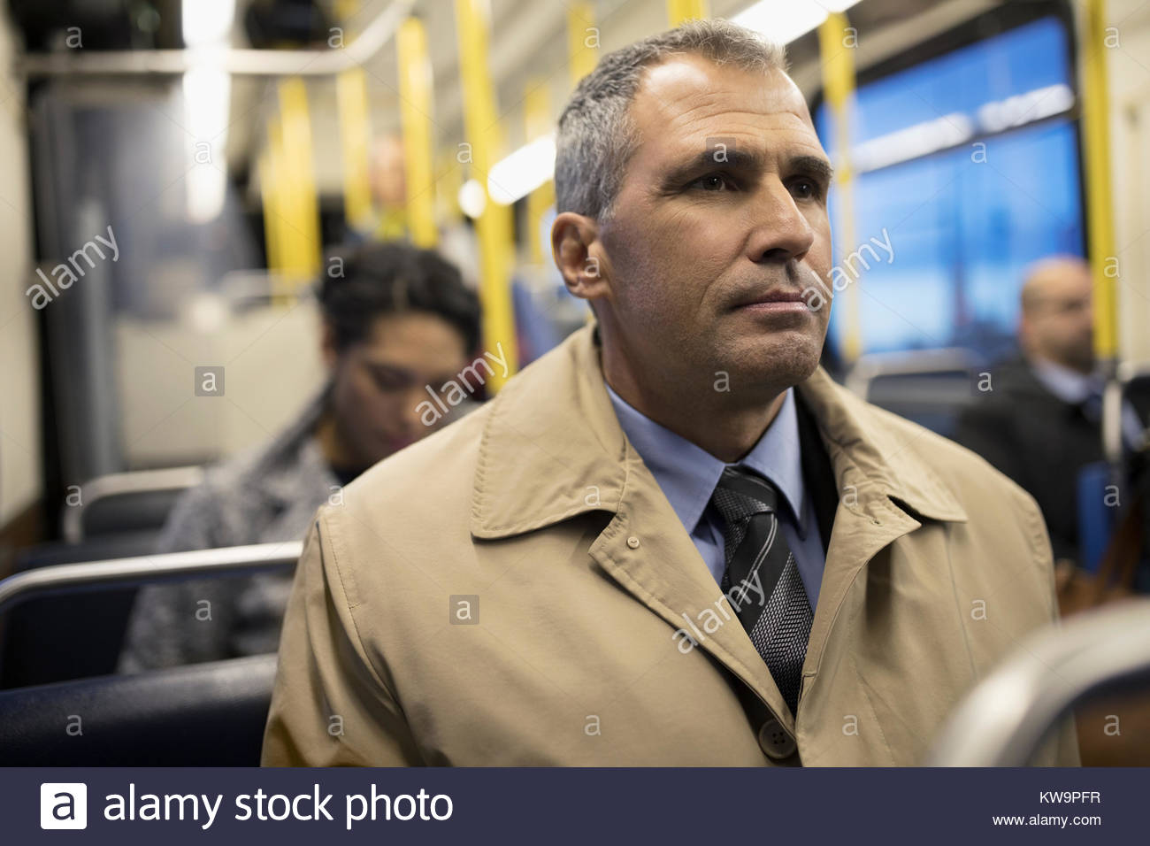 Serious mature businessman commuter riding bus - Stock Image