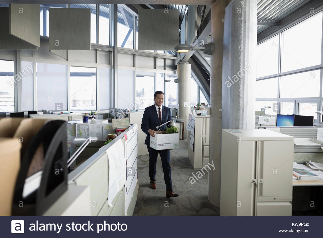 Businessman being laid off,carrying box of belongings in office - Stock Image