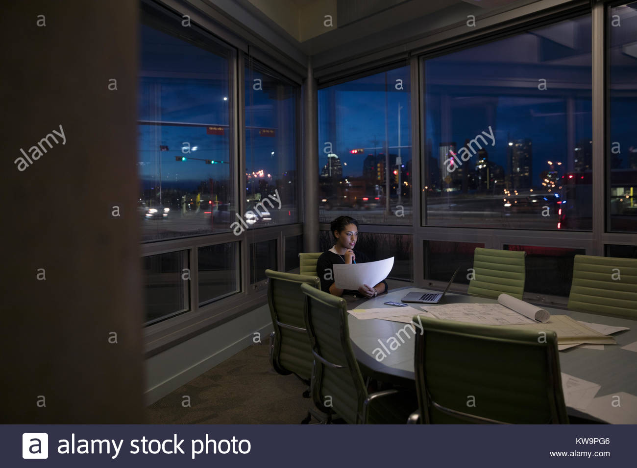 Dedicated female architect working late,reviewing blueprints in dark urban conference room - Stock Image