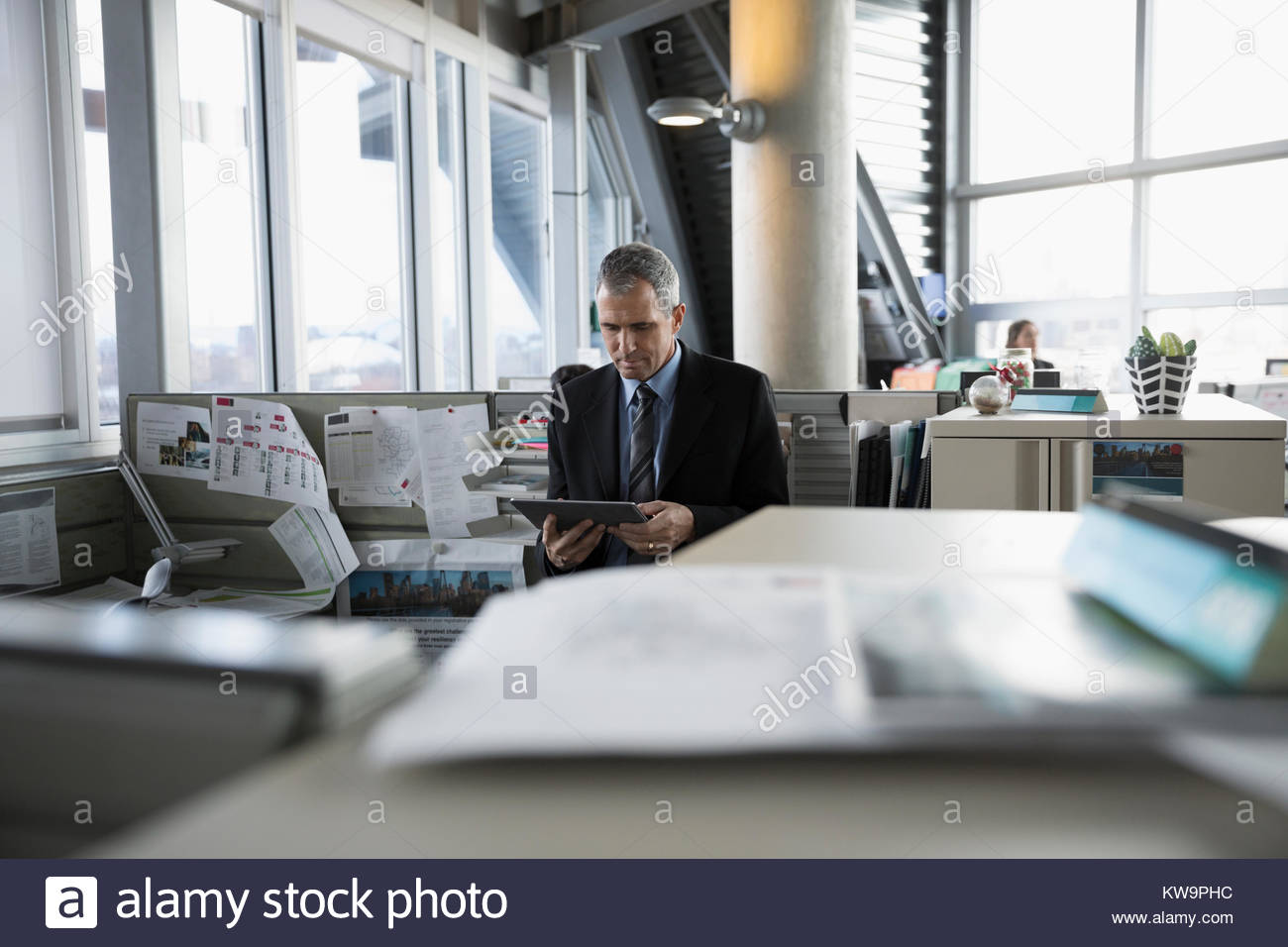Focused businessman using digital tablet in office cubicle - Stock Image