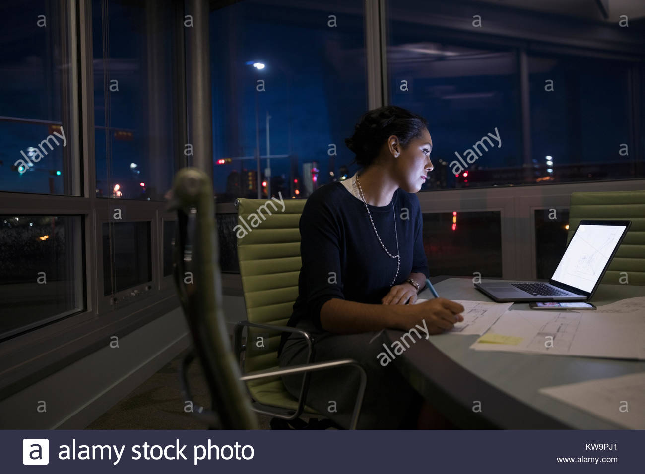 Dedicated female architect working late at laptop,editing blueprints in dark conference room - Stock Image
