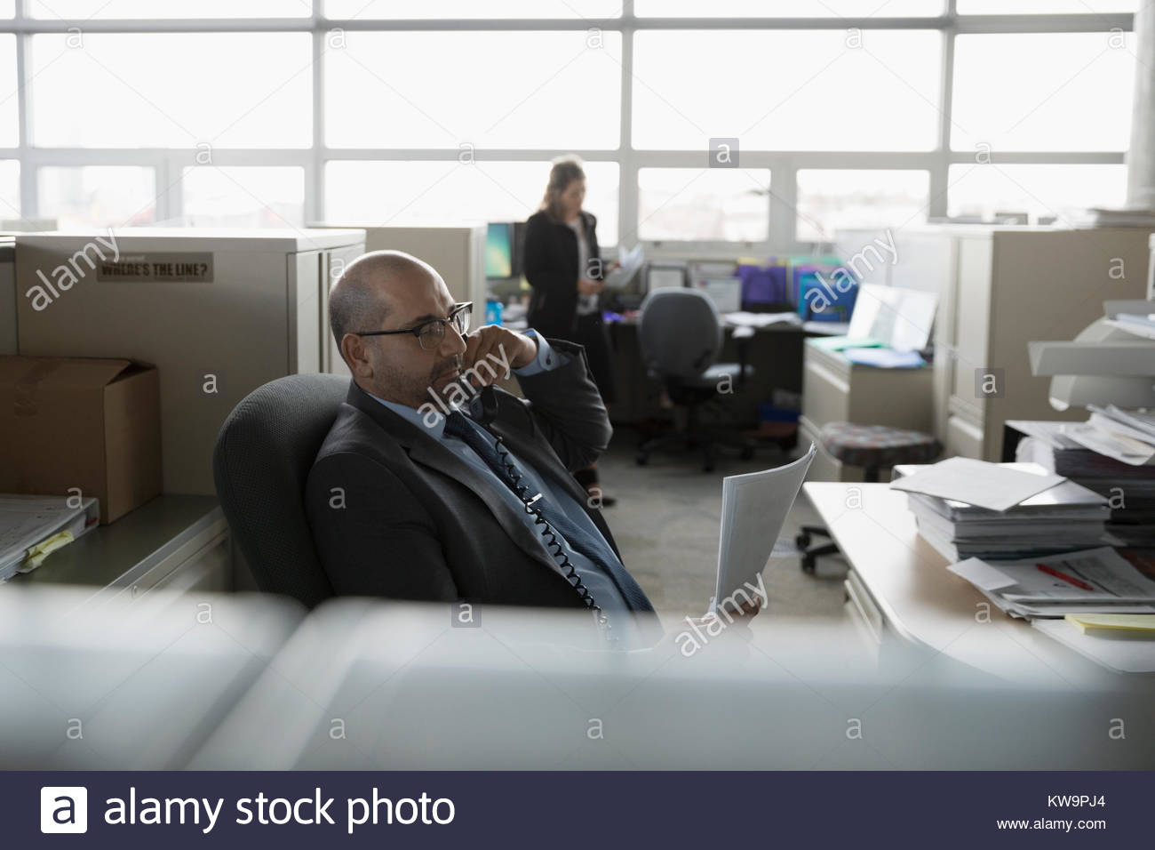 Businessman with paperwork talking on telephone in office cubicle - Stock Image