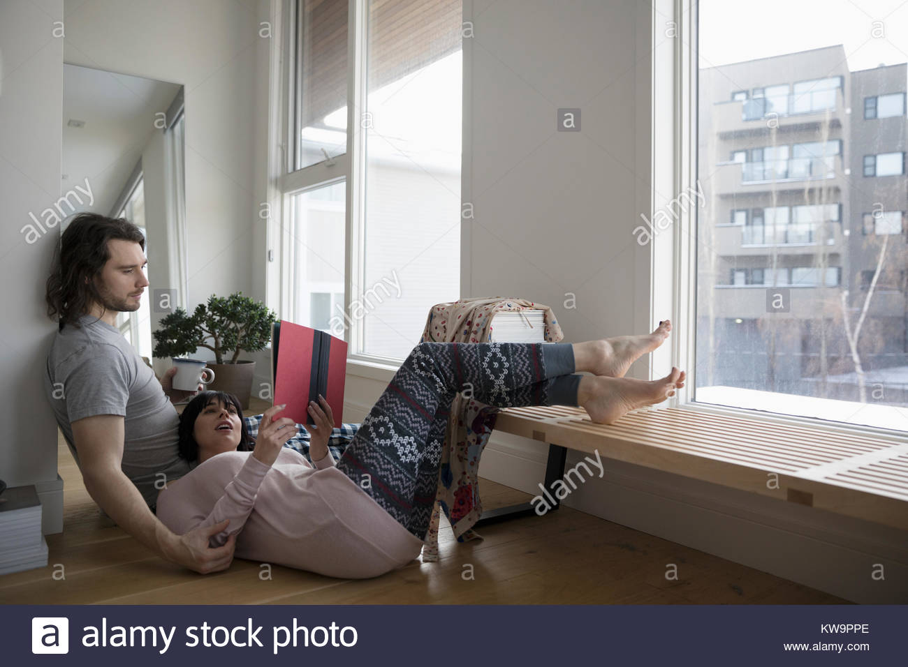 Affectionate couple in pajamas relaxing,drinking coffee and reading book on urban apartment floor - Stock Image
