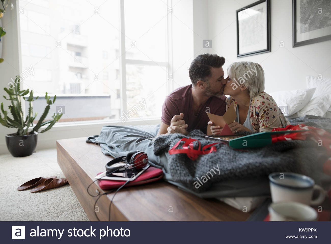Affectionate,romantic couple kissing and opening Valentine - Stock Image