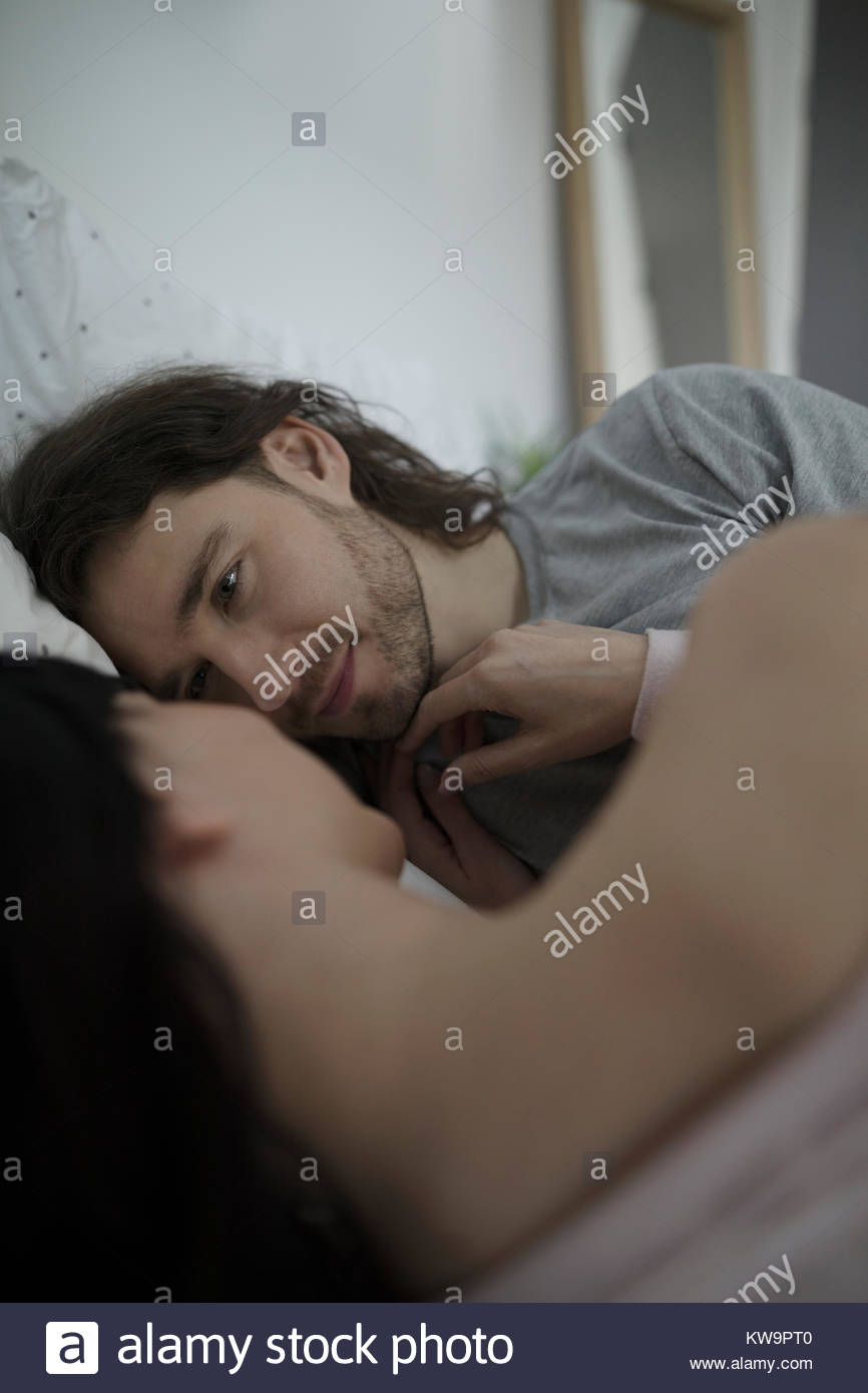 Affectionate,romantic couple cuddling face to face in bed - Stock Image
