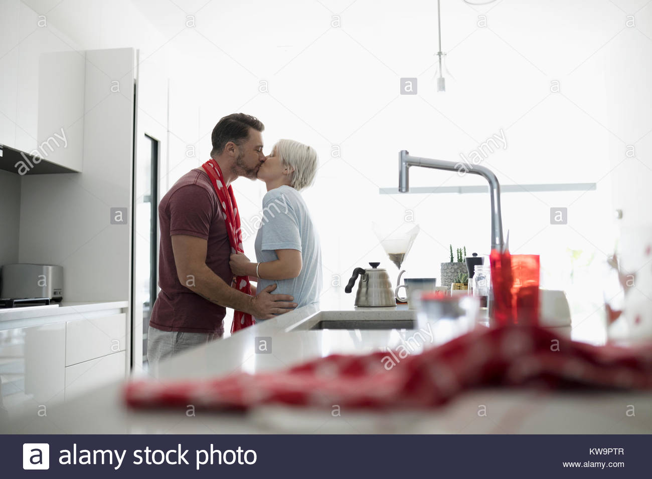Affectionate,romantic couple kissing in morning kitchen - Stock Image